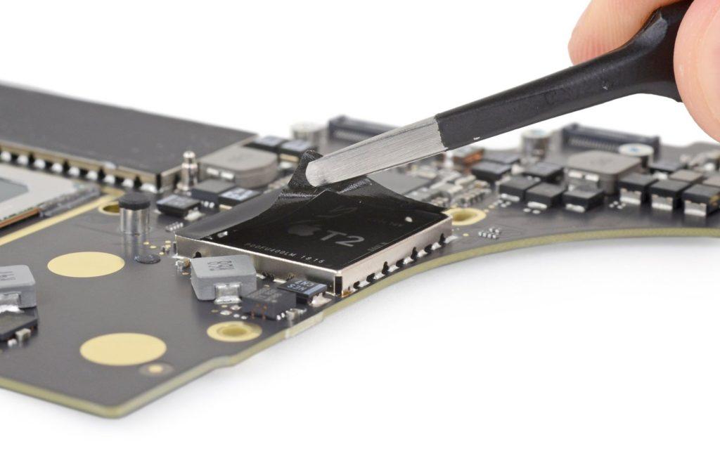 Пинцет, раскрывающий чип безопасности T2 на логической плате MacBook Pro.